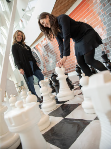 building strong culture - two women playing life-size chess