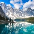 Landscape shot of a lake and mountains under blue sky with clouds, showcasing tourism in Alberta